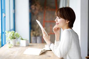 窓辺でタブレット端末を持つ若い女性の写真素材 [FYI02454724]