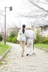 杖のシニア男性と歩く買い物袋を提げた後姿の女性ヘルパーの写真素材 [FYI02454777]