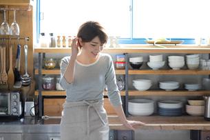 キッチンに佇む若い女性の写真素材 [FYI02454922]
