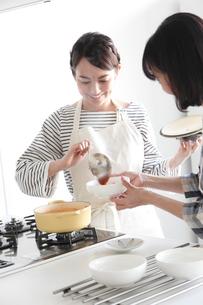 キッチンで料理をする母親と娘の写真素材 [FYI02455125]