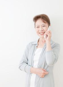 携帯電話で話す60代の女性の写真素材 [FYI02457071]