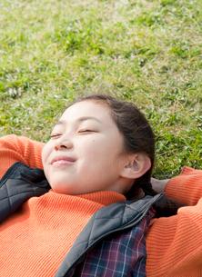 芝生に寝転ぶ小学生の女の子の写真素材 [FYI02457101]