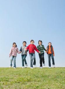 芝生を歩く小学生の男の子2人と女の子3人の写真素材 [FYI02457129]