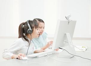 パソコンを操作する小学生の女の子2人の写真素材 [FYI02457172]