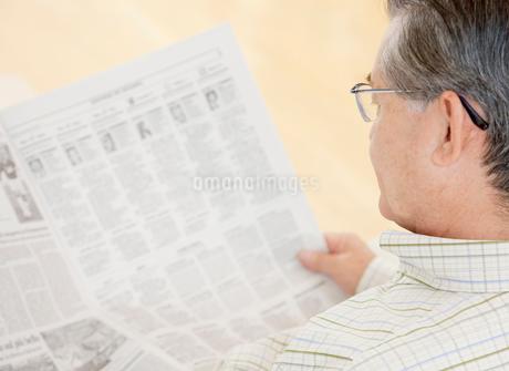 新聞を読む60代の男性の写真素材 [FYI02457174]