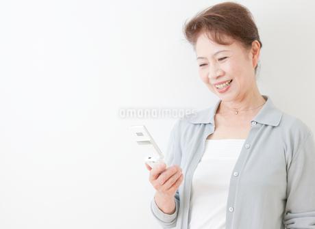 携帯電話を操作する60代の女性の写真素材 [FYI02457191]