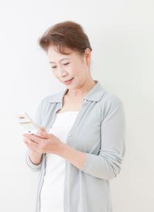 携帯電話を操作する60代の女性の写真素材 [FYI02457223]