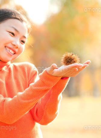 紅葉の中で栗を持つ小学生の女の子の写真素材 [FYI02457225]