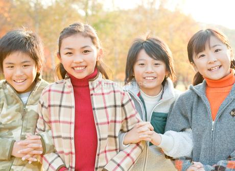 紅葉の中にいる仲の良い小学生の写真素材 [FYI02457266]