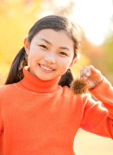 紅葉の中で栗を持つ小学生の女の子の写真素材 [FYI02457274]