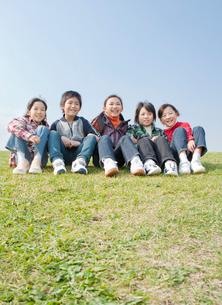 芝生に座る小学生の男の子2人と女の子3人の写真素材 [FYI02457287]