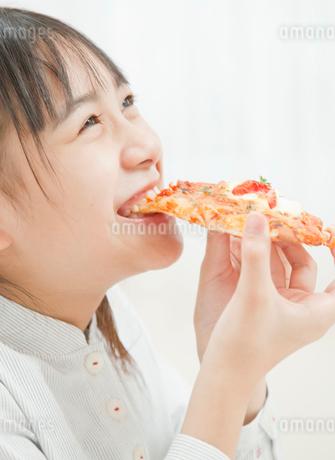 ピザを食べる小学生の女の子の写真素材 [FYI02457348]