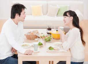 ダイニングテーブルで食事を楽しむ新婚夫婦 ダイニングの写真素材 [FYI02457489]