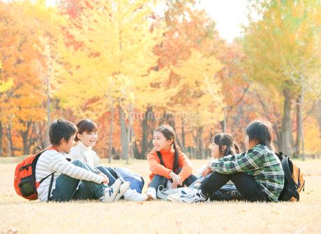 紅葉の中で遠足を楽しむ小学生の写真素材 [FYI02457496]