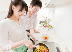 料理をする新婚夫婦 IHキッチンの写真素材 [FYI02457502]