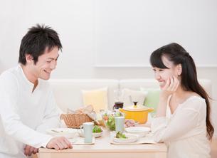 ダイニングテーブルで食事を楽しむ新婚夫婦 ダイニングの写真素材 [FYI02457527]