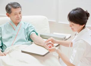 シニア男性の脈を計る看護師の写真素材 [FYI02457532]