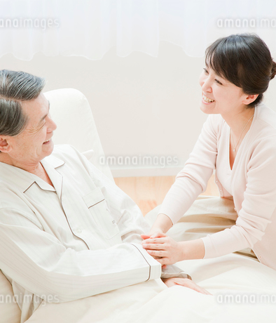 ベッドに入った父親と会話する娘の写真素材 [FYI02457552]