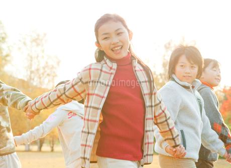 紅葉の中で輪になって回る小学生の写真素材 [FYI02457566]