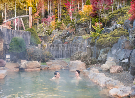 露天風呂に入る60代の夫婦と紅葉の写真素材 [FYI02457569]