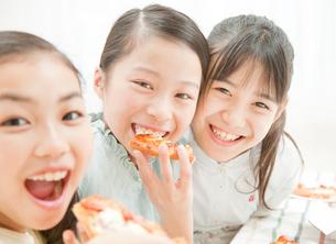 ピザを食べる小学生の女の子の写真素材 [FYI02457583]
