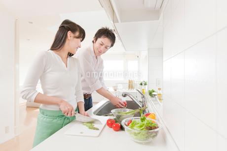 料理をする新婚夫婦 キッチンの写真素材 [FYI02457639]