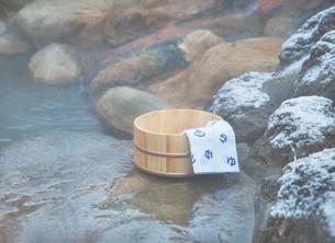 桶と手ぬぐい 雪の温泉イメージの写真素材 [FYI02457675]