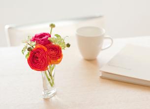 食卓の上に飾られた花と本とカップの写真素材 [FYI02457713]