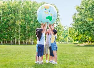 緑の中で地球儀を持ち上げる小学生の男の子と女の子の写真素材 [FYI02457741]
