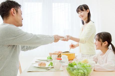 ダイニングテーブルで食事をする家族の写真素材 [FYI02457754]