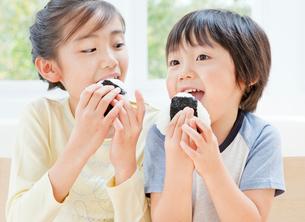 おにぎりを食べる女の子と男の子の姉弟の写真素材 [FYI02457761]
