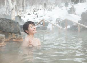 雪と露天風呂に入る20代女性の写真素材 [FYI02457763]