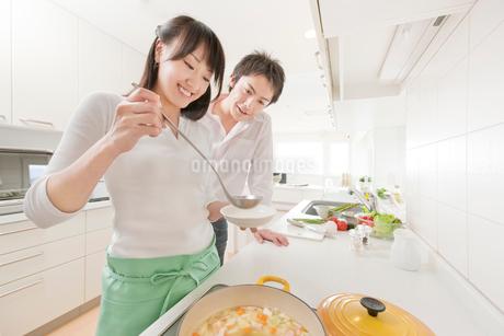 料理をする新婚夫婦 IHキッチンの写真素材 [FYI02457792]