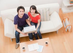 パソコンをする新婚夫婦 リビングの写真素材 [FYI02457799]