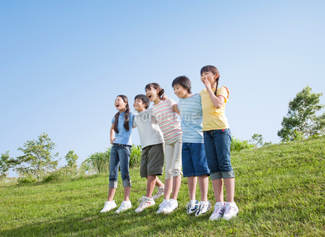 青空のもと肩を組む5人の小学生の写真素材 [FYI02457812]