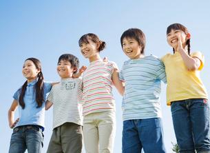 青空のもと肩を組む5人の小学生の写真素材 [FYI02457848]