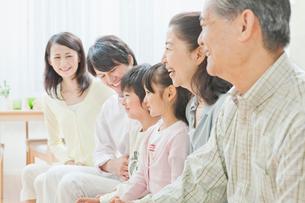 ソファーで団らんする三世代家族の写真素材 [FYI02457879]