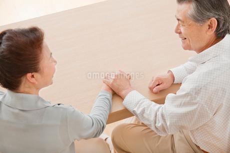 見つめ合って手を重ねるシニア夫婦の写真素材 [FYI02457934]