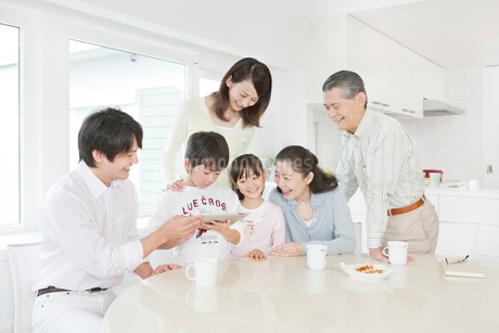リビングでiPadを操作する三世代家族の写真素材 [FYI02457944]