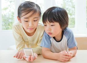 携帯電話を見る女の子と男の子の姉弟の写真素材 [FYI02457956]