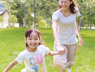新緑の中、手をつないで走る母子の写真素材 [FYI02457978]