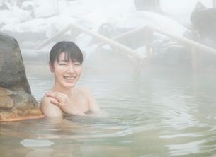雪と露天風呂に入る20代女性の写真素材 [FYI02457999]
