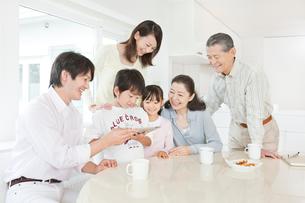 リビングでiPadを操作する三世代家族の写真素材 [FYI02458012]