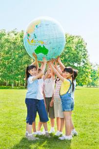 緑の中 地球儀を持ち上げる小学生の男の子と女の子の写真素材 [FYI02458030]