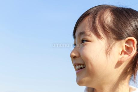 青空のもとの6歳の女の子 ポートレートの写真素材 [FYI02458048]