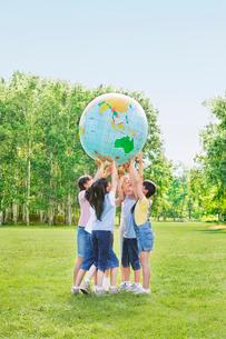緑の中で地球儀を持ち上げる小学生の男の子と女の子の写真素材 [FYI02458110]