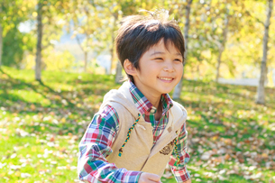 紅葉の中、走る6歳の男の子の写真素材 [FYI02458163]
