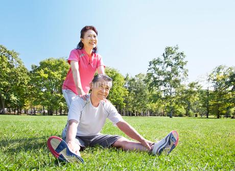 緑の中でストレッチをする60代シニア夫婦の写真素材 [FYI02458175]