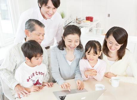 リビングでパソコンを操作する三世代家族の写真素材 [FYI02458194]