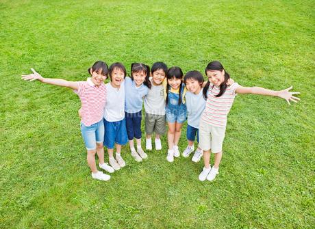 芝生で肩を組む7人の小学生の男の子と女の子 俯瞰の写真素材 [FYI02458209]